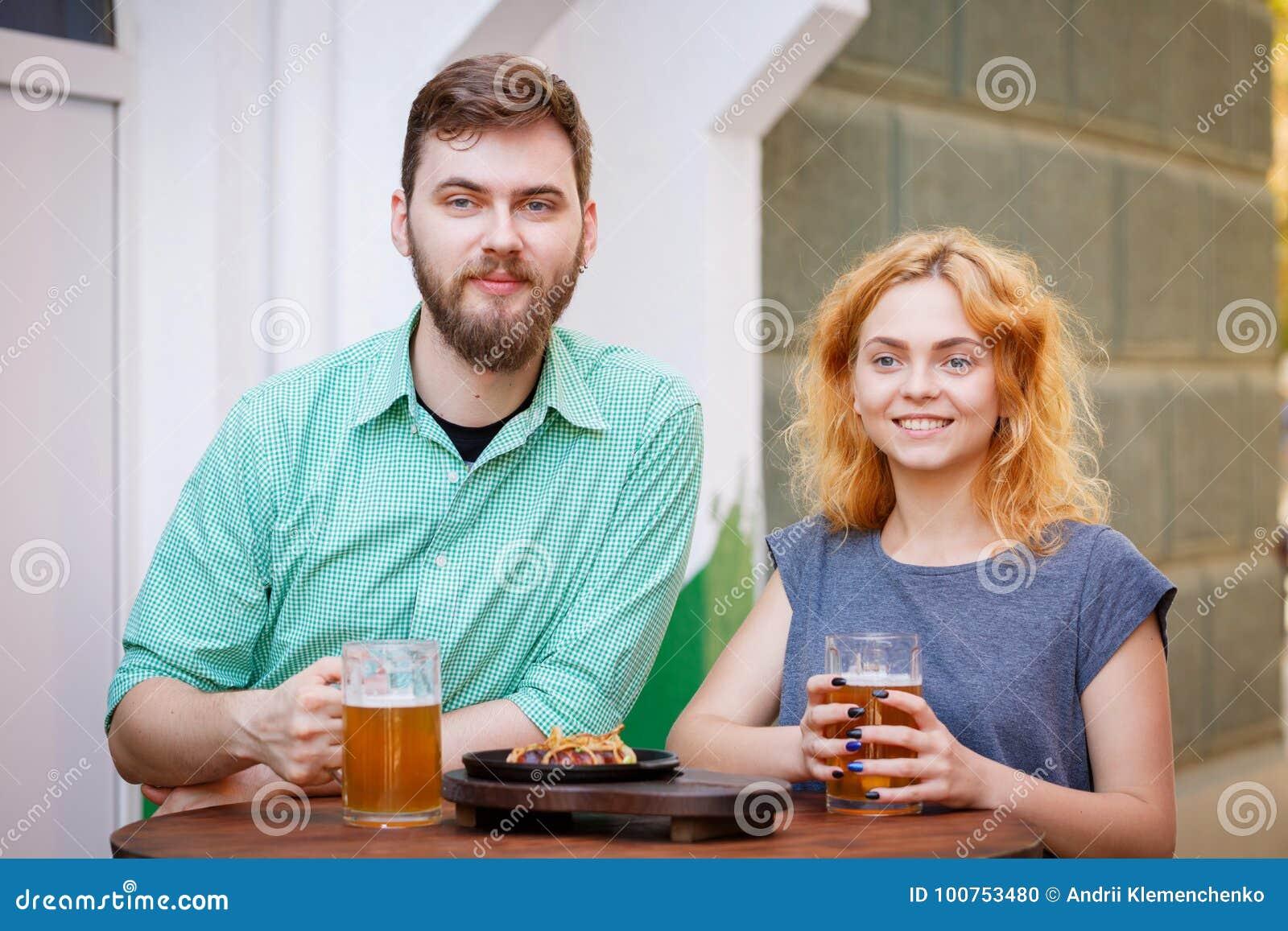 Couples gracieux heureux détendant dans le bar et buvant de la bière