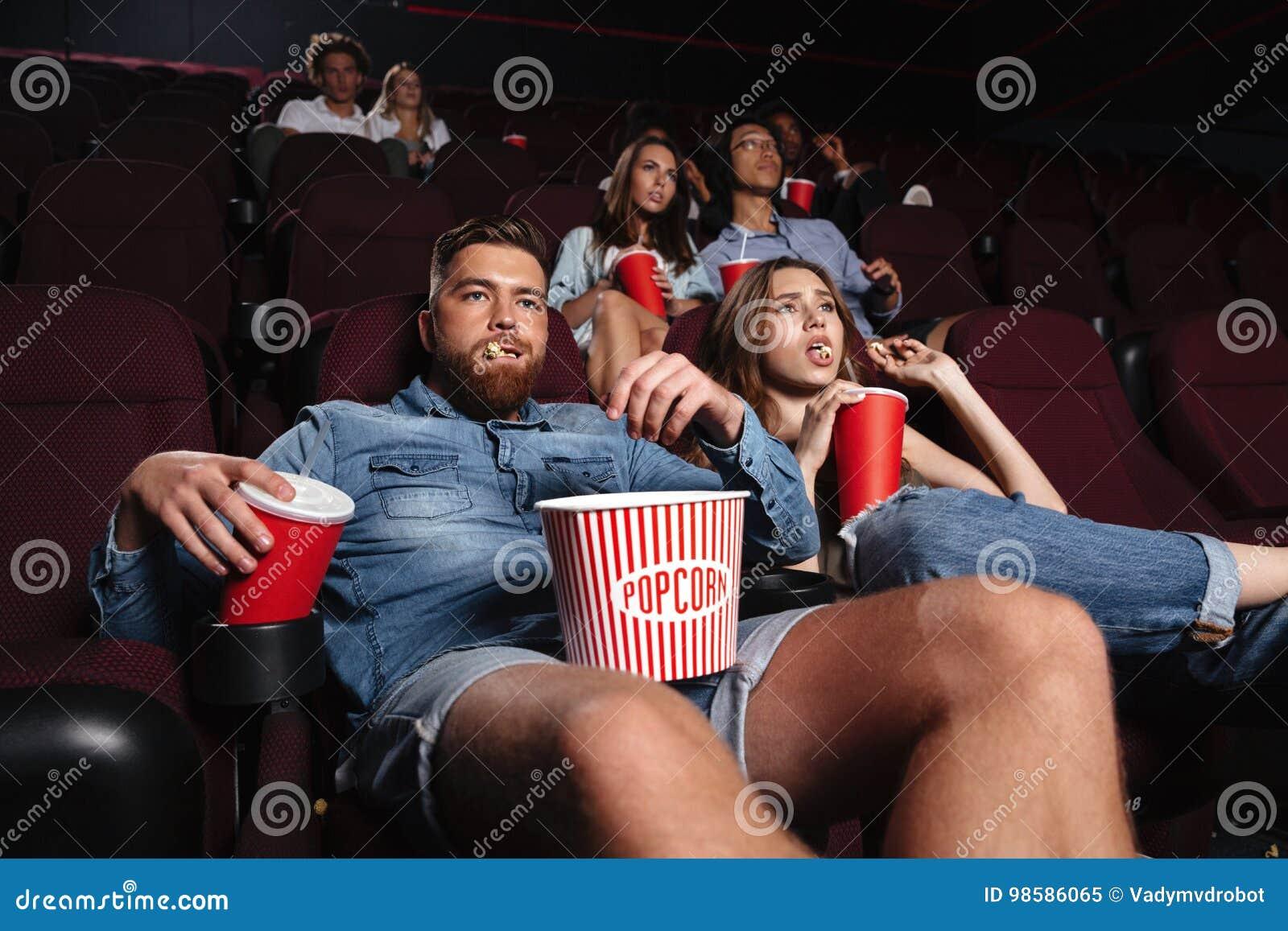Couples grossiers impolis se reposant dans un cinéma