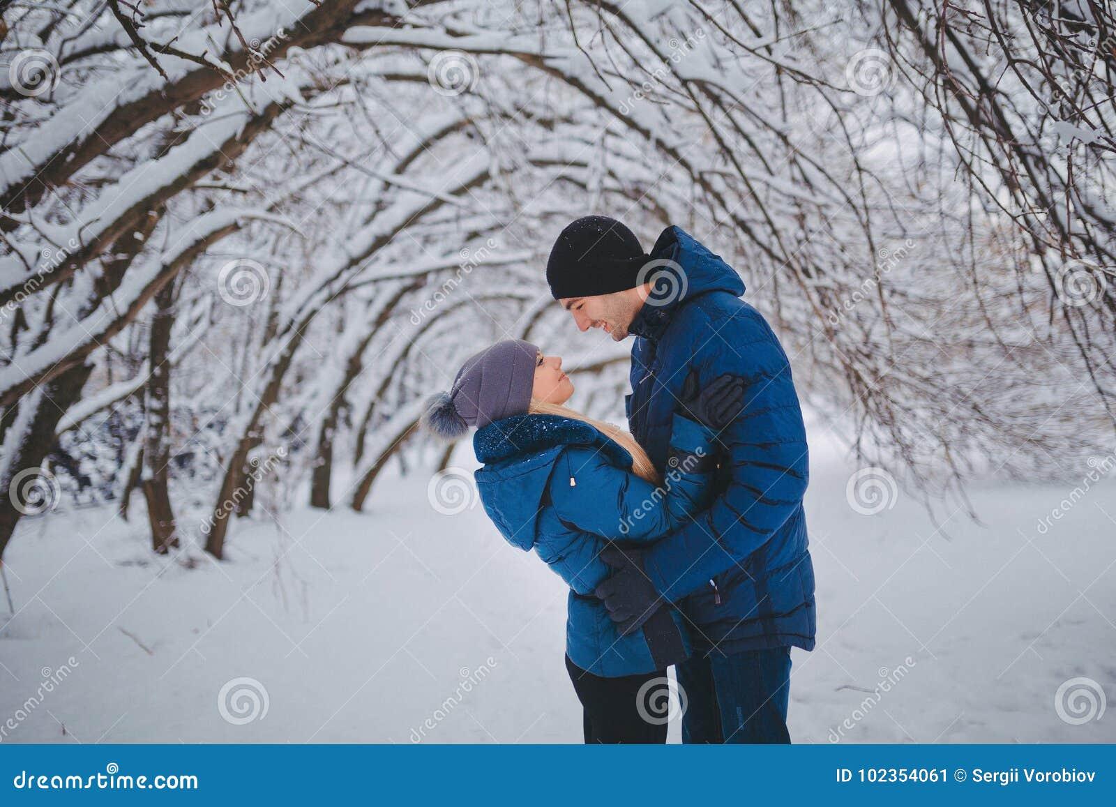 Couples heureux ayant l amusement et l embrassant dehors dans le parc de neige Vacances de l hiver