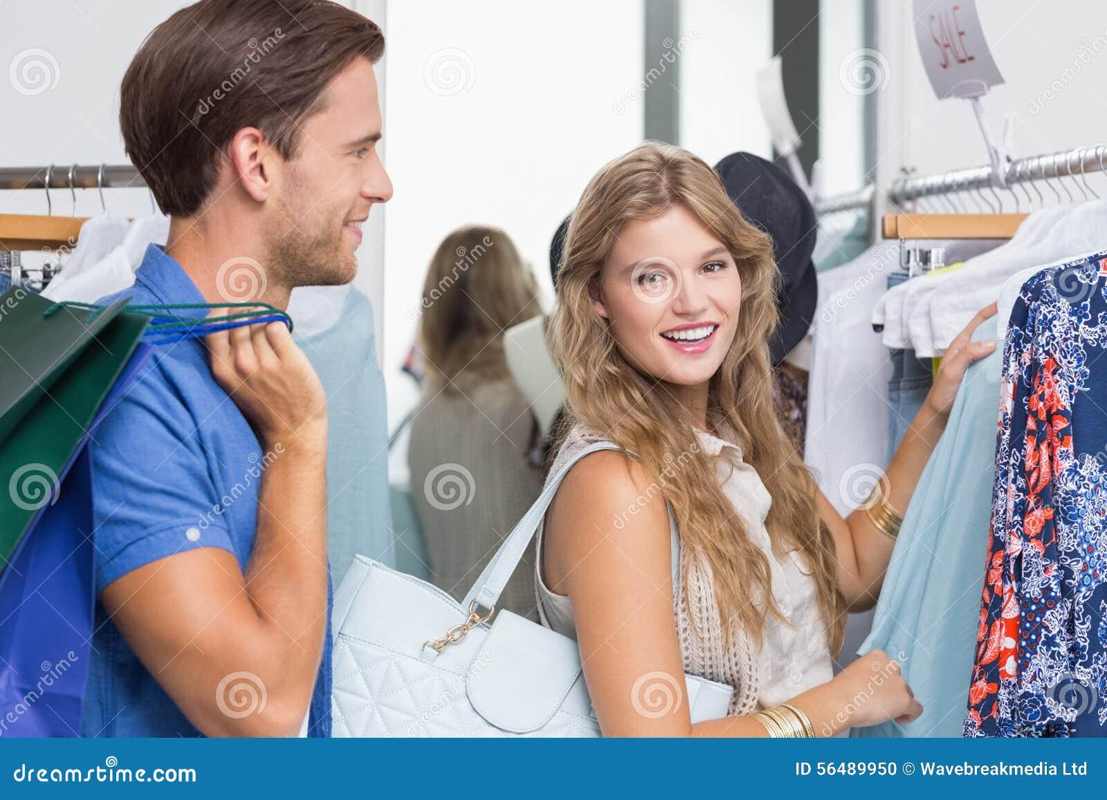 Couples heureux choisissant de nouveaux vêtements
