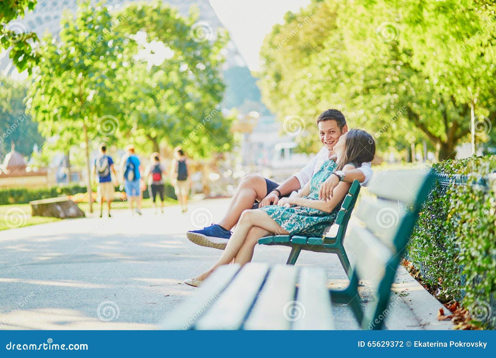 Couples heureux de datation sur un banc en parc parisien
