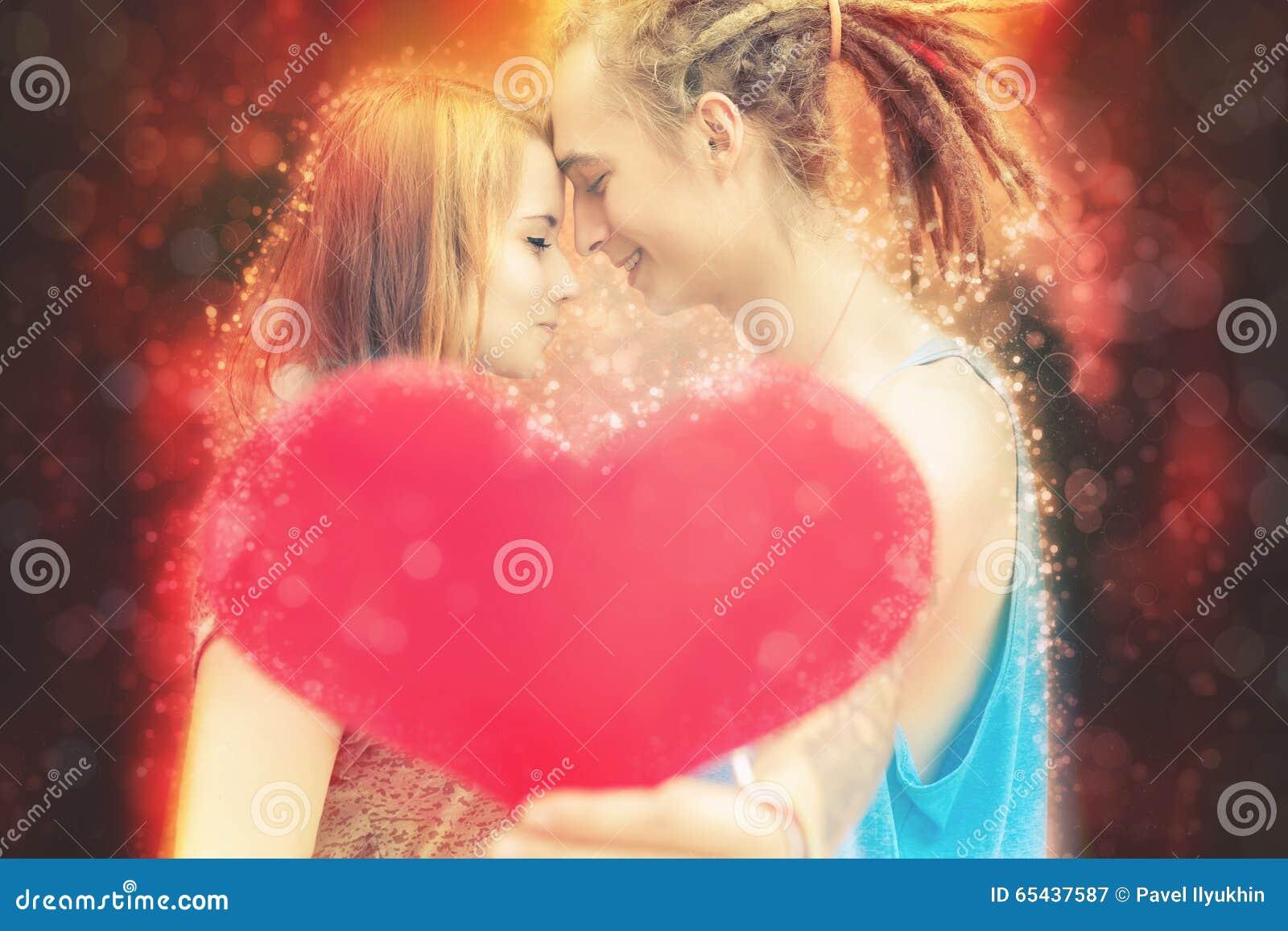 Couples heureux de jour de valentines tenant le symbole rouge de coeur