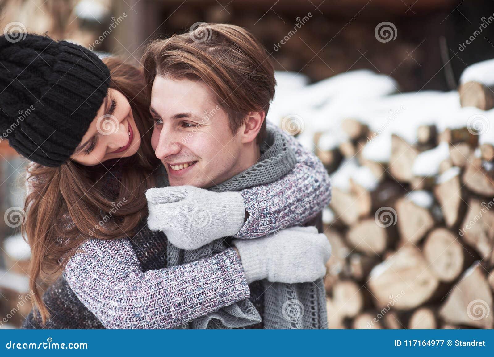 Couples heureux de Noël dans l étreinte d amour dans la forêt froide d hiver neigeux, l espace de copie, célébration de partie de