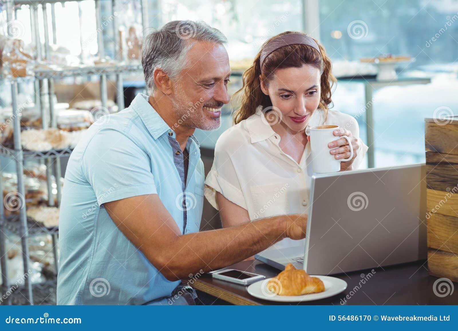 Couples heureux dirigeant quelque chose sur l ordinateur portable