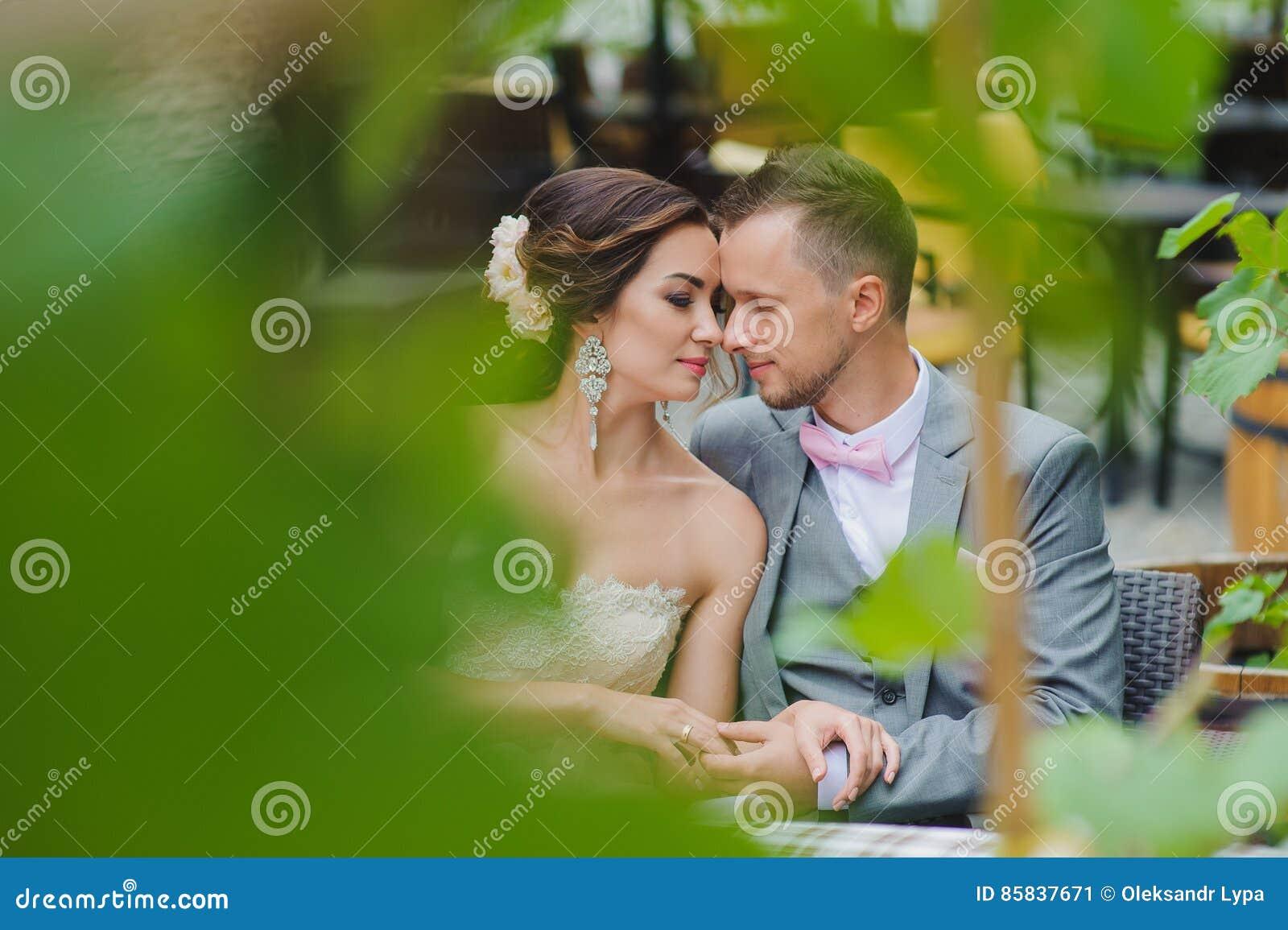 Couples heureux embrassant tout en se reposant en café de rue