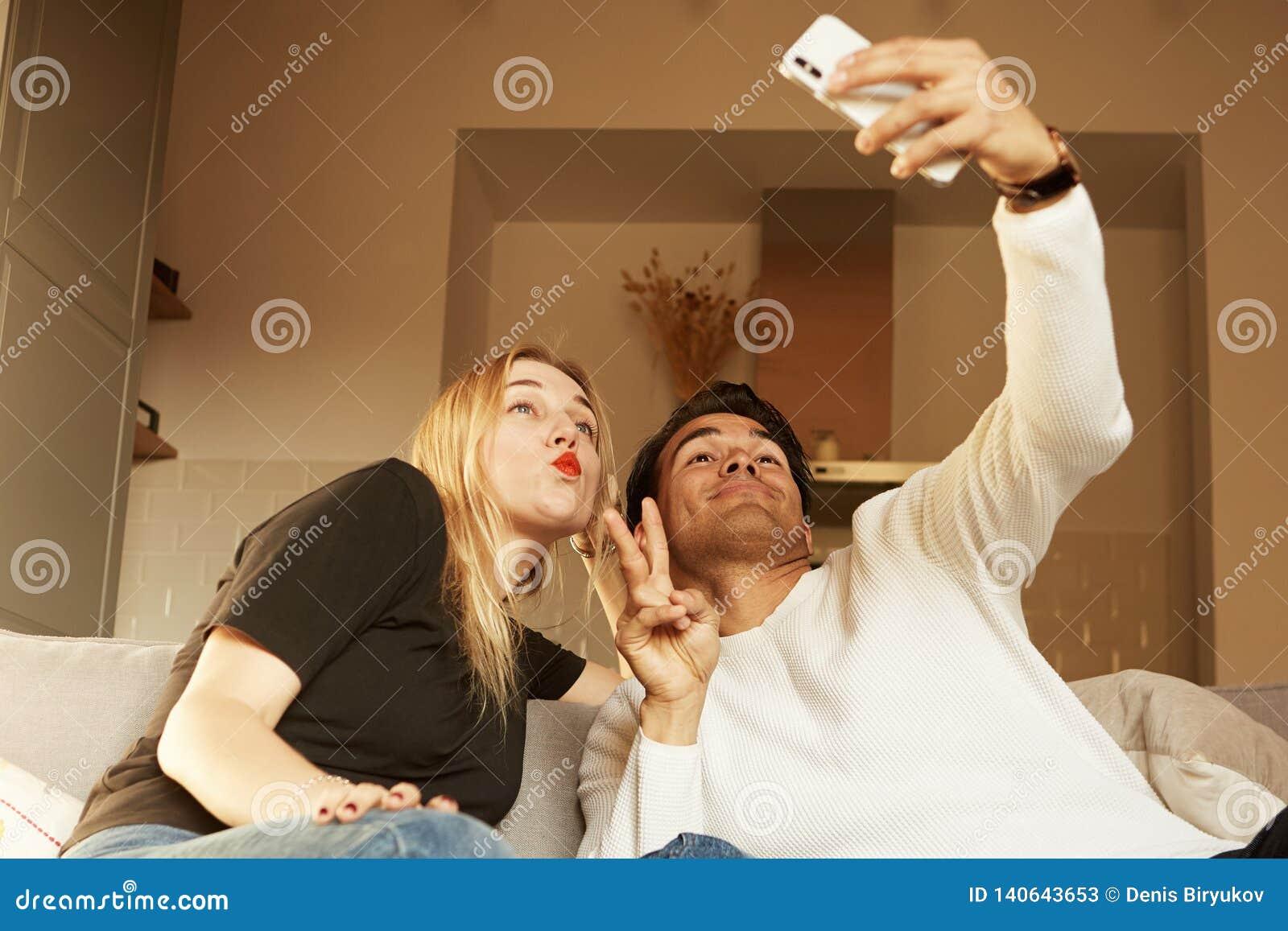 Couples heureux gais aimants prenant le selfie sur le sofa à la maison