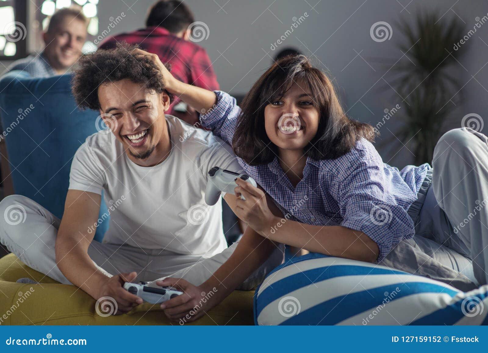 Couples heureux jouant des jeux vidéo au bureau de démarrage moderne