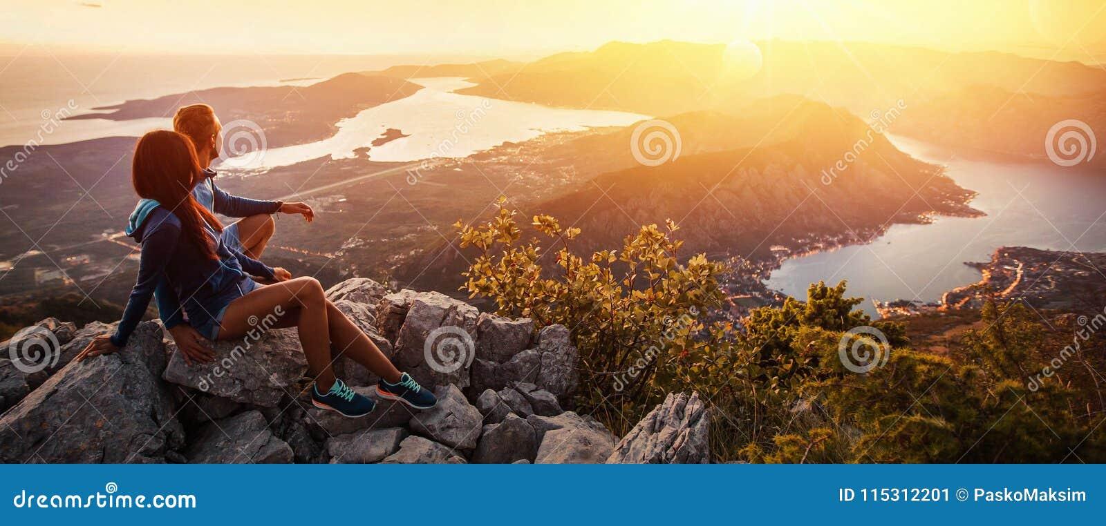 Couples heureux observant le coucher du soleil dans les montagnes
