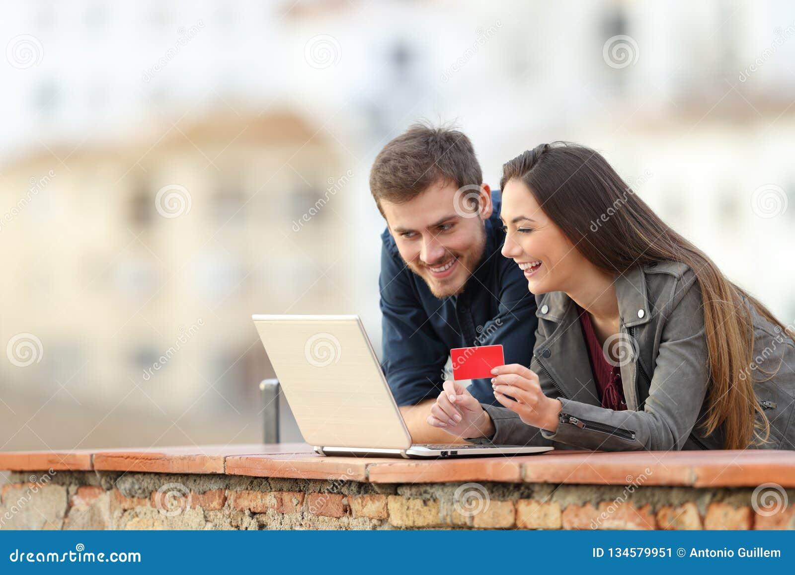 Couples heureux payant en ligne avec la carte de crédit et l ordinateur portable