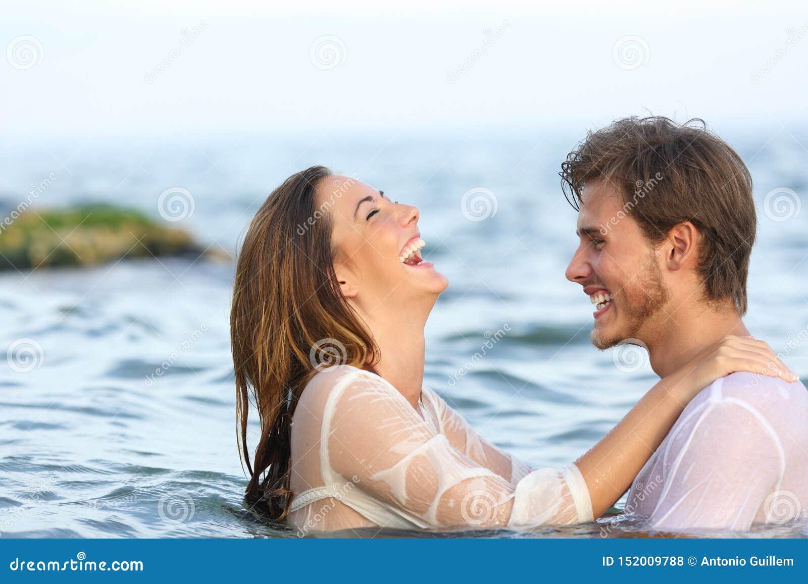 Couples heureux plaisantant dans l eau sur la plage