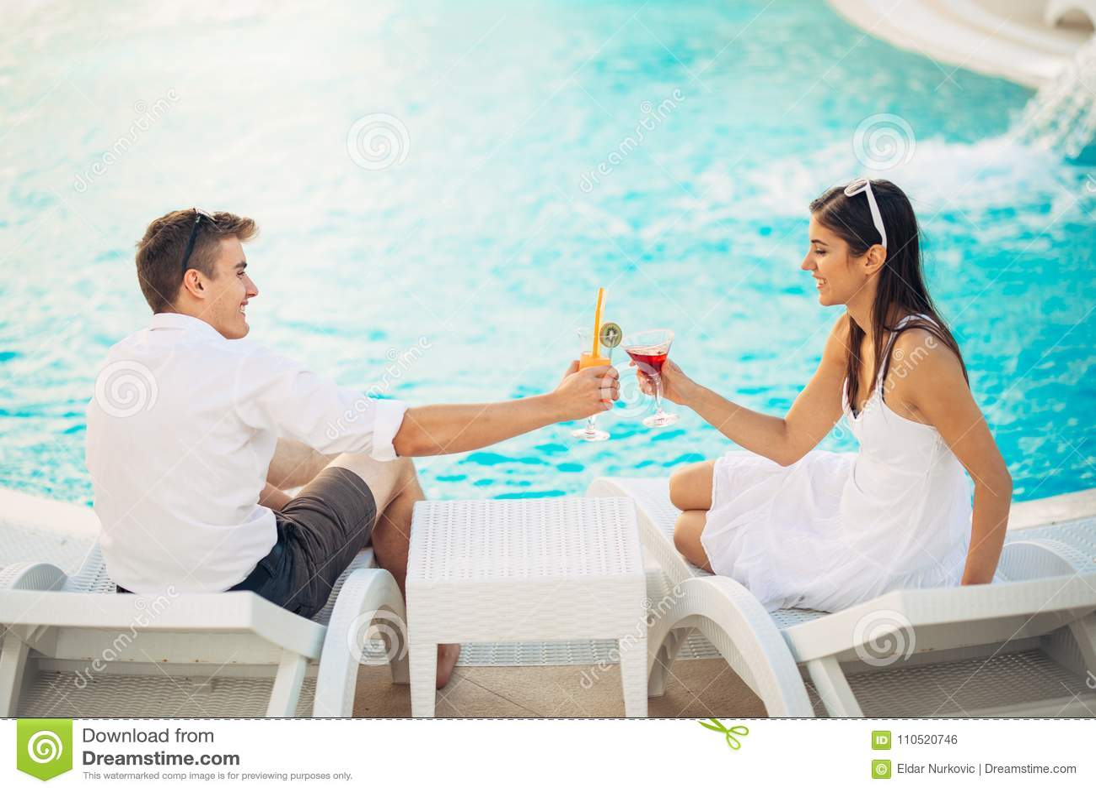 Couples heureux positifs ayant un après-midi romantique par la piscine dans le lieu de villégiature de luxe d été Cocktails potab