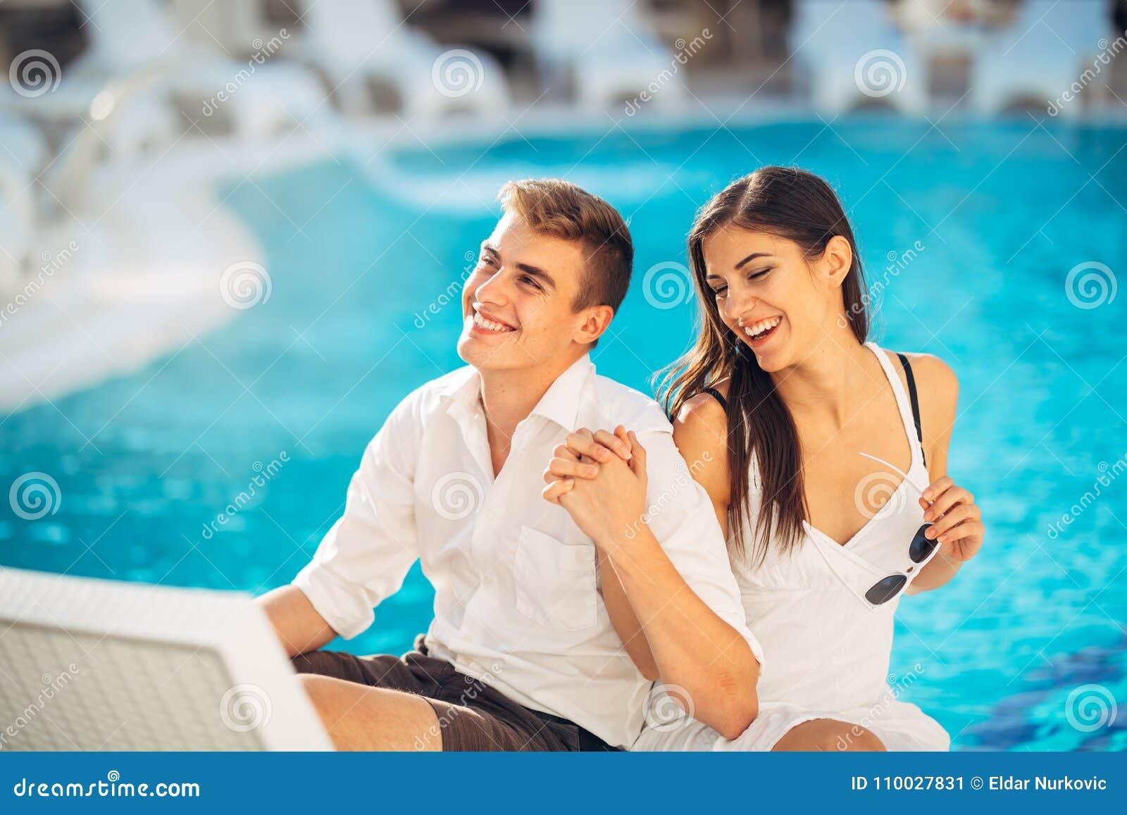 Couples heureux positifs détendant par la piscine dans le lieu de villégiature de luxe d été Appréciant le temps ensemble au cent