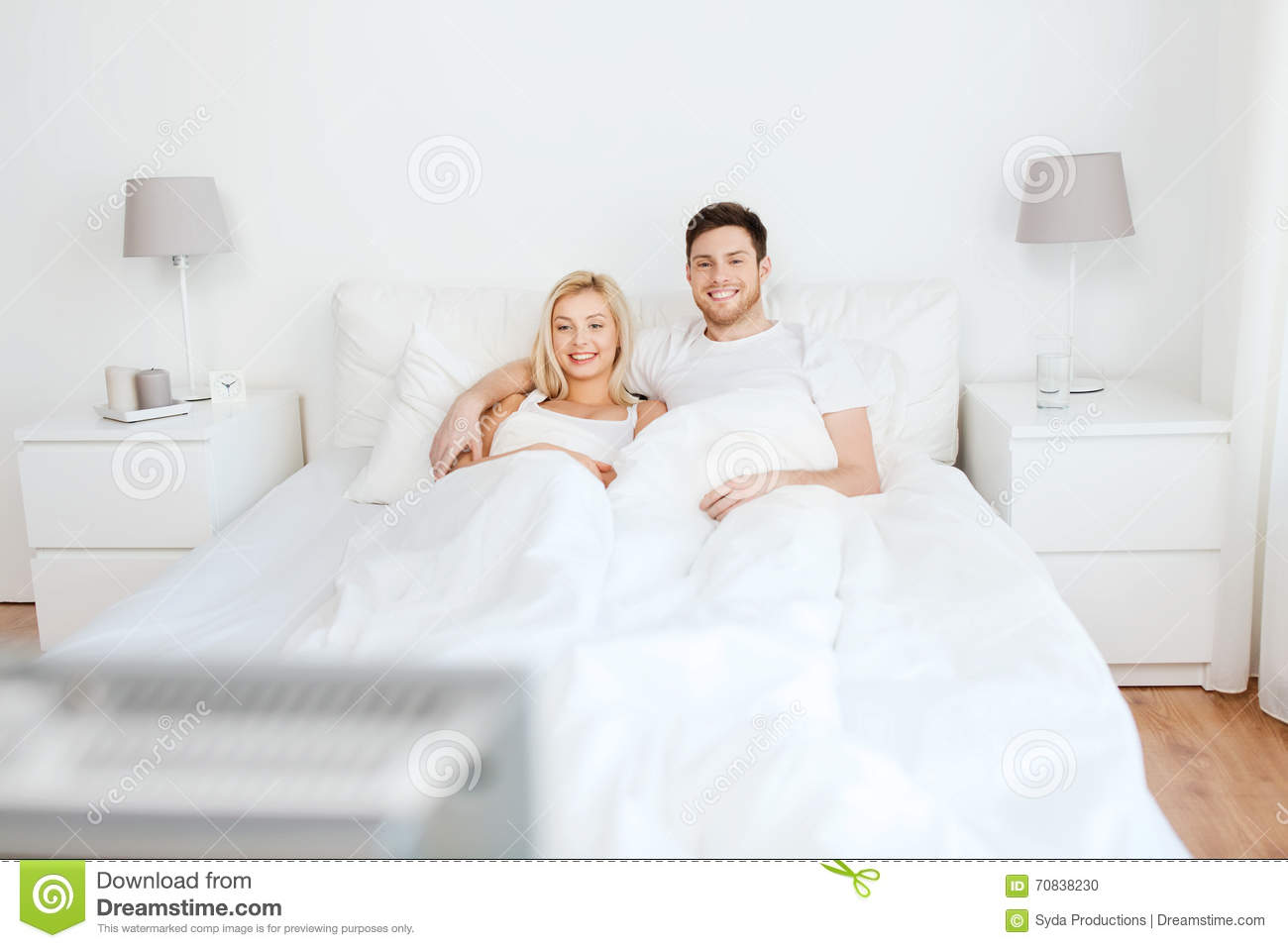 couples heureux se situant dans le lit la maison et la tv de observation photo stock image. Black Bedroom Furniture Sets. Home Design Ideas