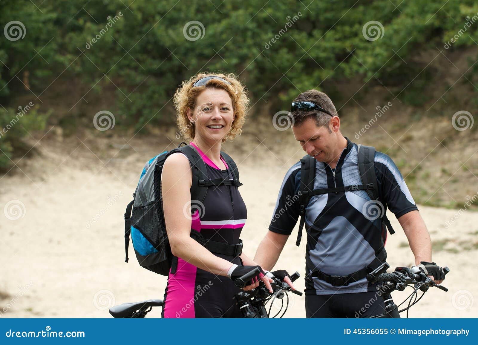 Couples heureux se tenant dehors avec des vélos
