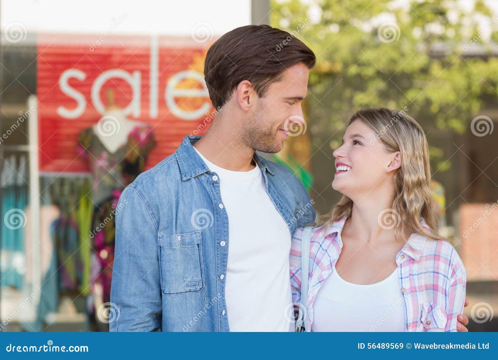 Couples heureux se tenant devant un signe de VENTE