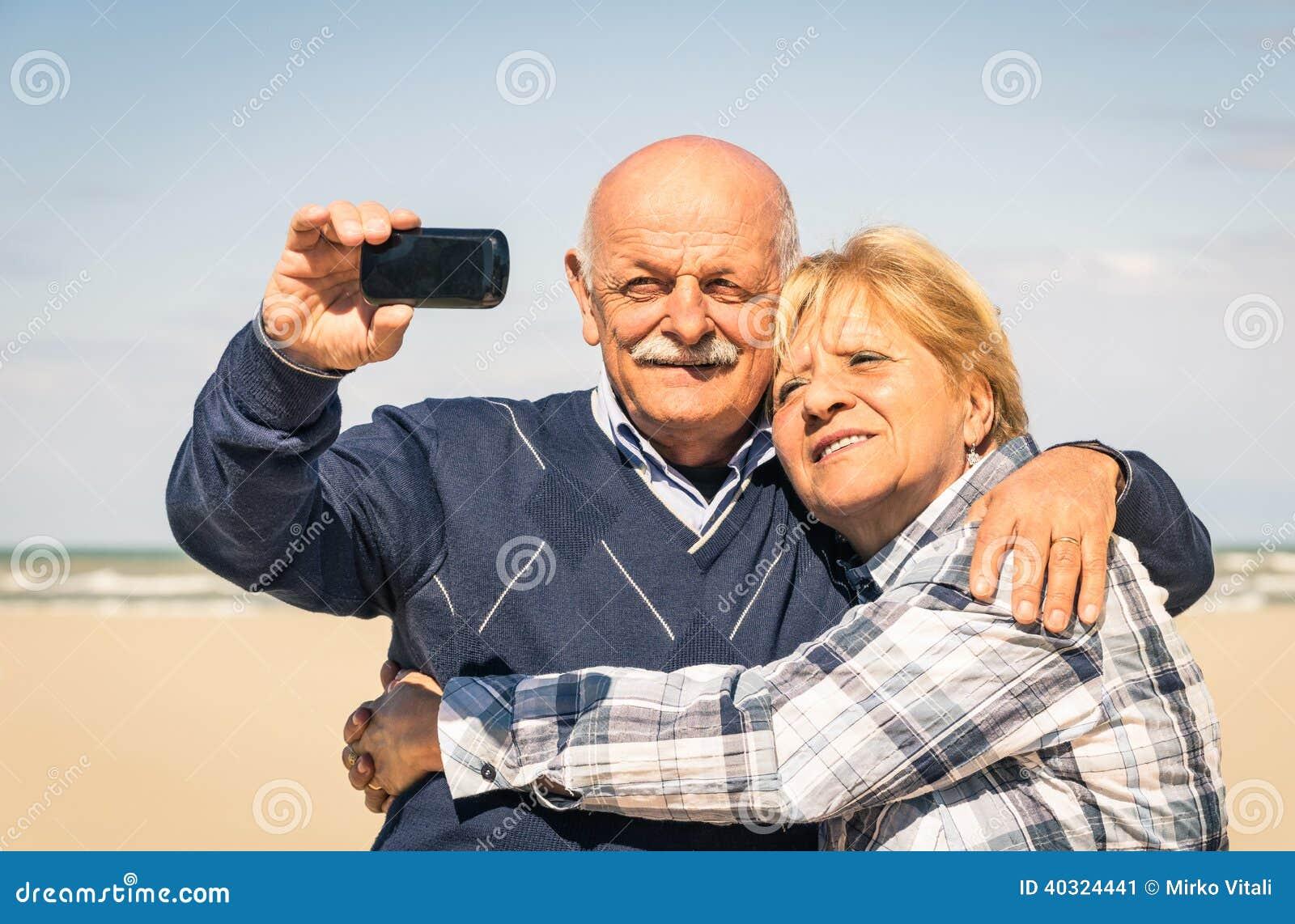 Couples heureux supérieurs prenant un selfie à la plage
