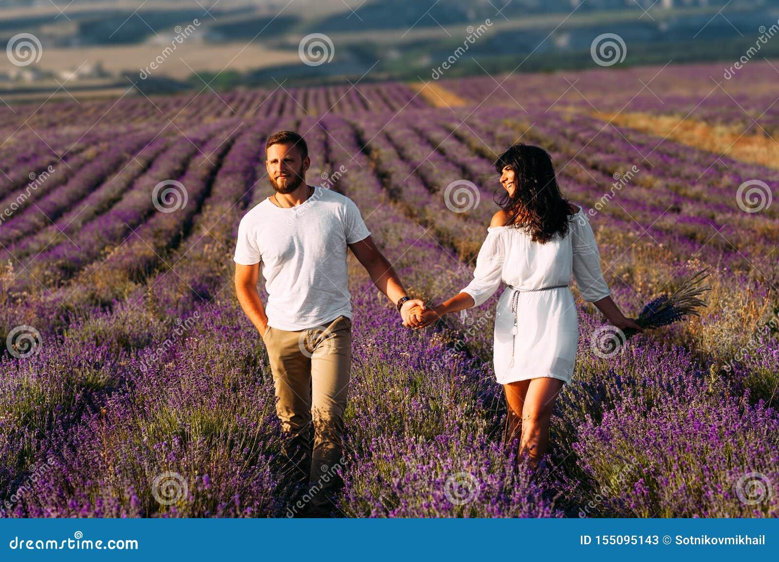Couples heureux tenant des mains dans des domaines de lavande Couples dans l amour sur des gisements de fleur Voyage de lune de m