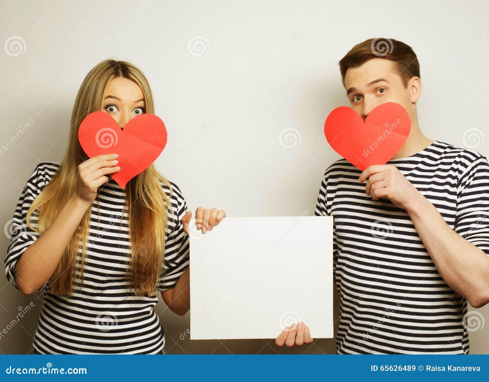 Couples heureux tenant les coeurs vides et rouges blancs