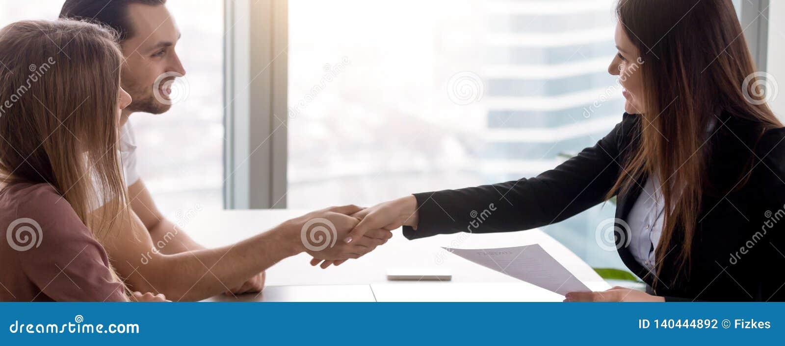 Couples horizontaux d image signant la poignée de main de contrat d immobiliers avec l agent immobilier