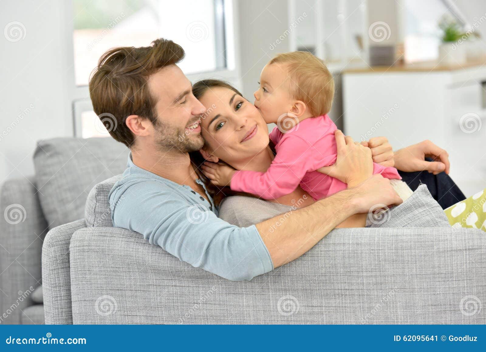 couples jouant avec le b b sur le sofa photo stock image 62095641. Black Bedroom Furniture Sets. Home Design Ideas