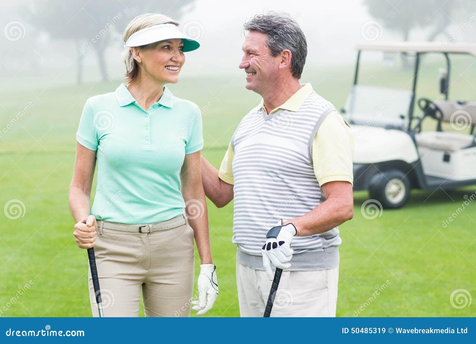 Couples jouants au golf heureux se faisant face avec le boguet de golf derrière