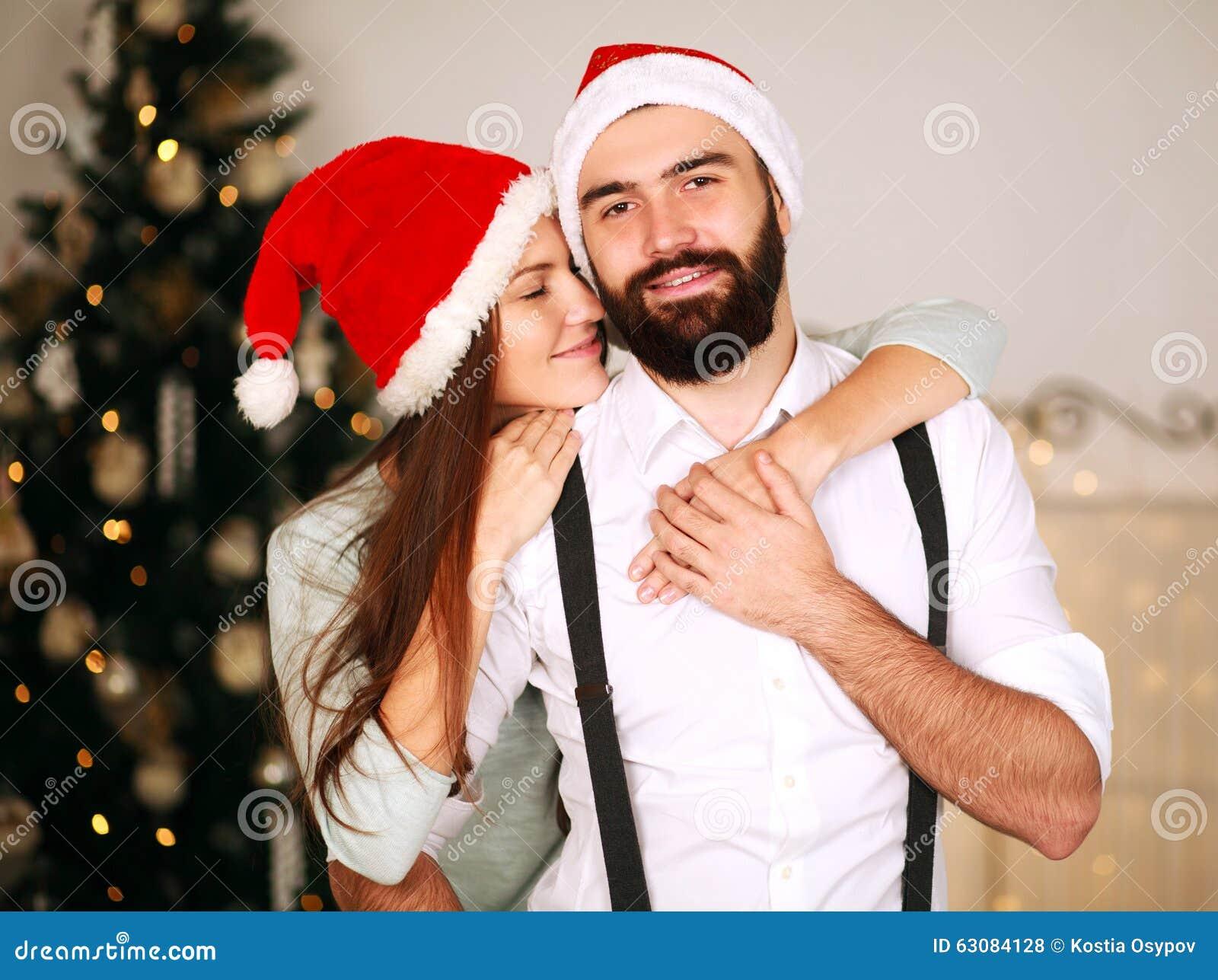 Download Couples Joyeux Dans Des Chapeaux Rouges Sur Le Fond De L'arbre De Noël Photo stock - Image du hommes, personne: 63084128
