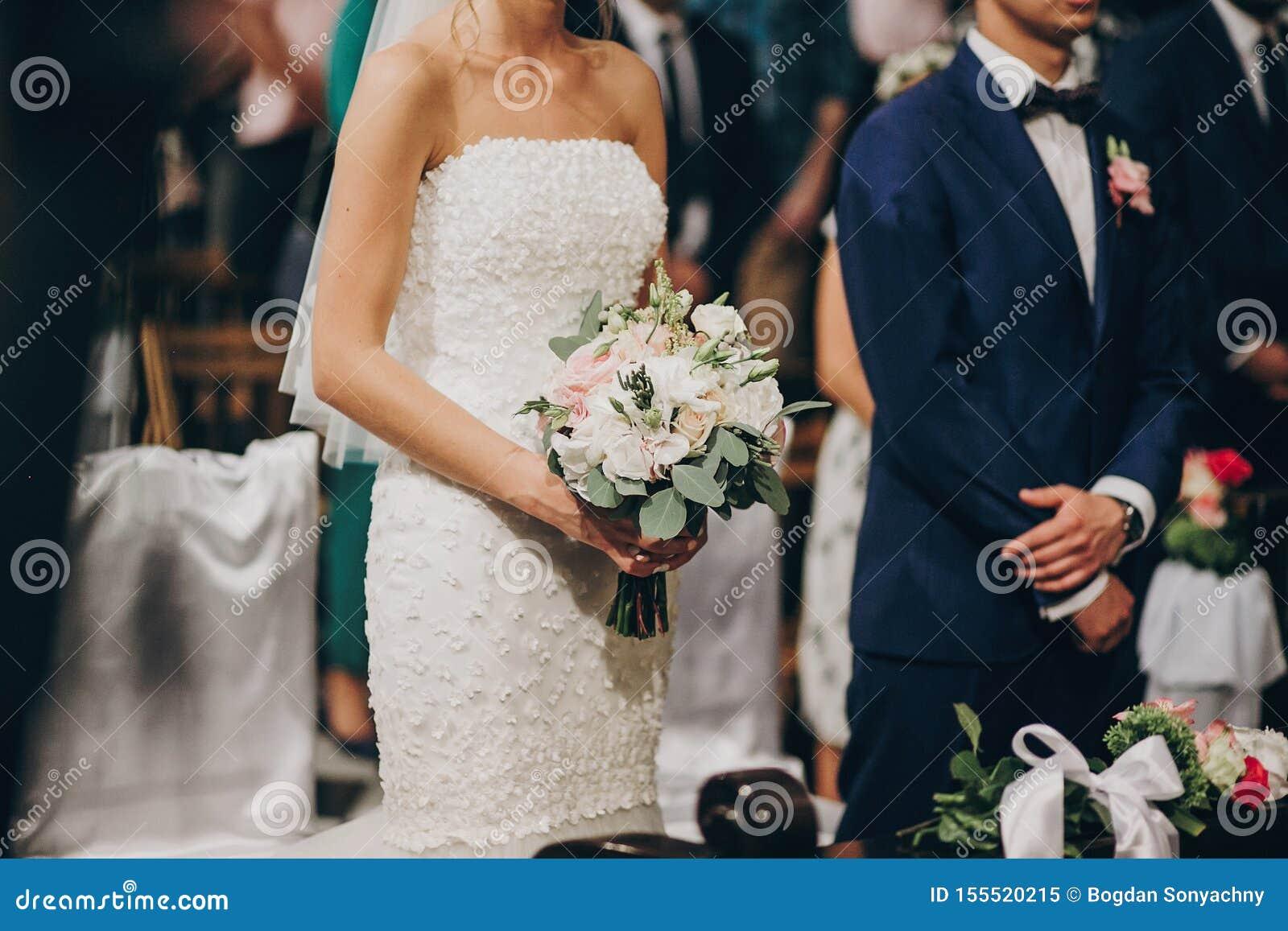 Couples les épousant élégants se tenant dans l église pour le mariage saint Beaux jeunes mariés priant à l autel en bois dans l é