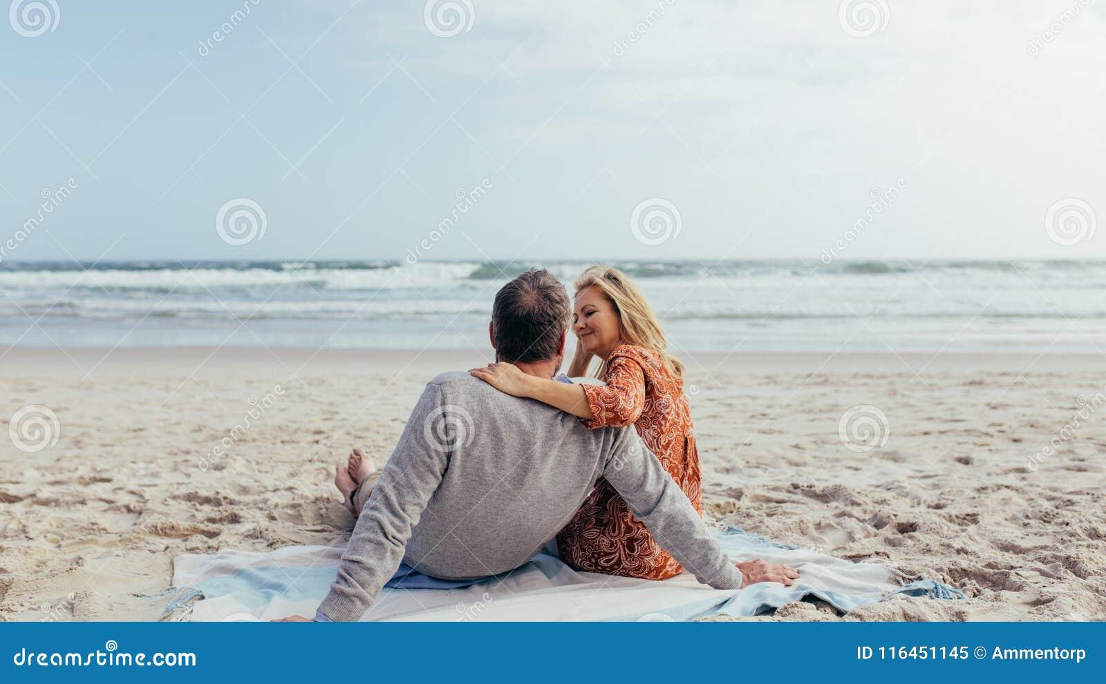 Couples mûrs passant le temps sur la plage
