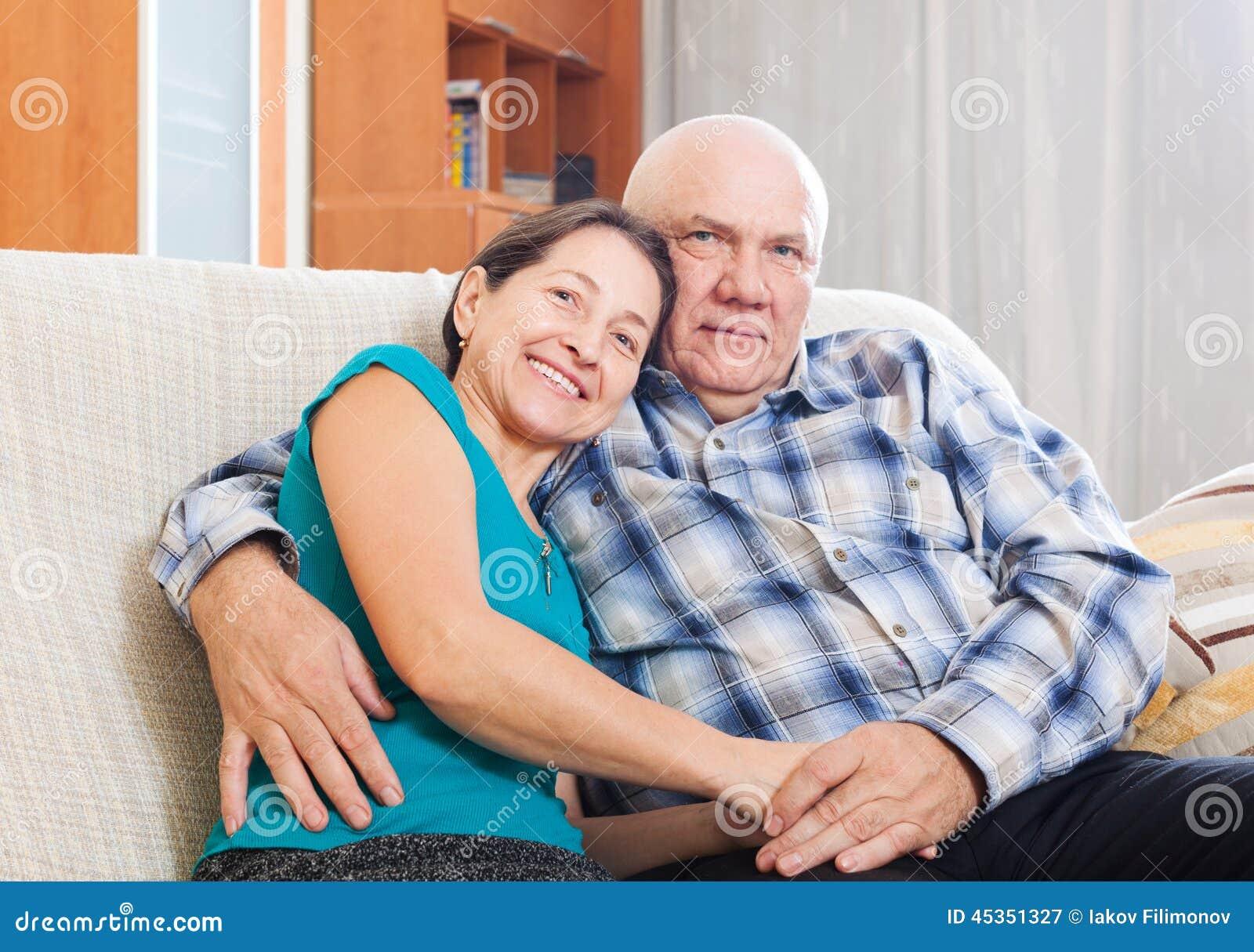 Couples mûrs affectueux sur le sofa