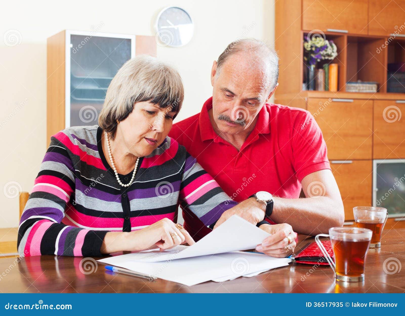 Couples mûrs lisant le document financier