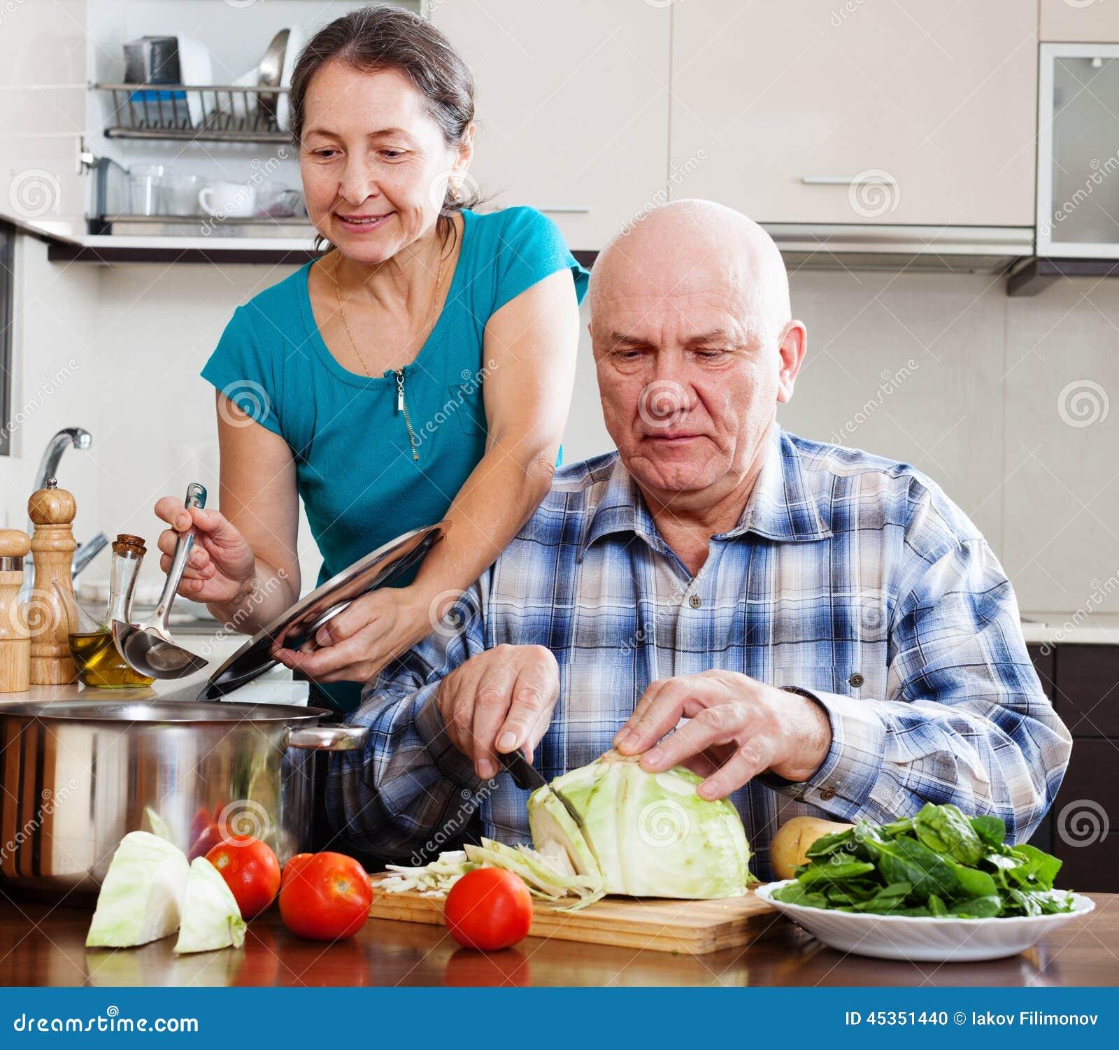Couples mûrs ordinaires faisant cuire avec des légumes
