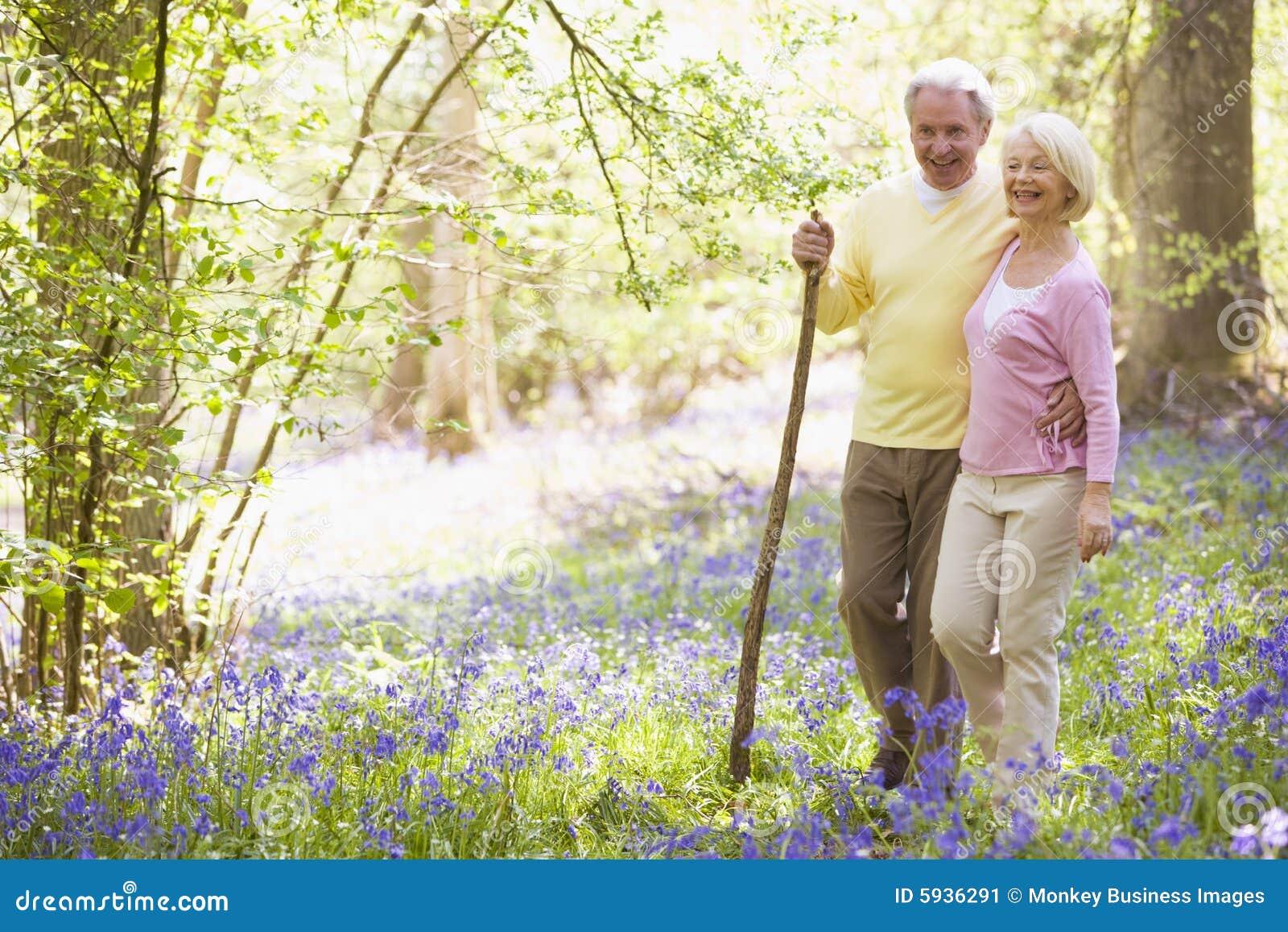 Couples marchant à l extérieur avec le sourire de bâton de marche