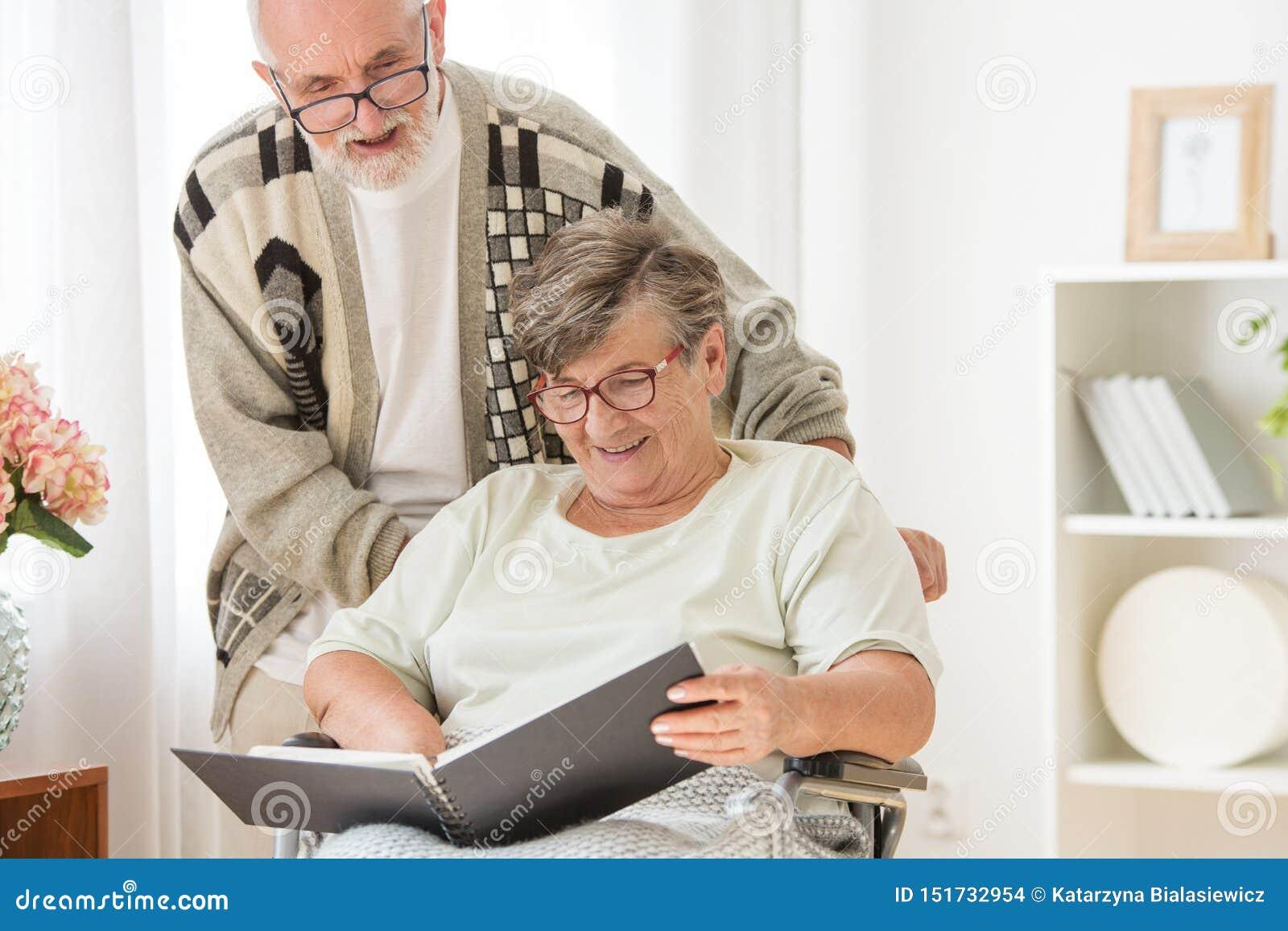 Couples mariés supérieurs heureux avec l album photos à la maison de repos