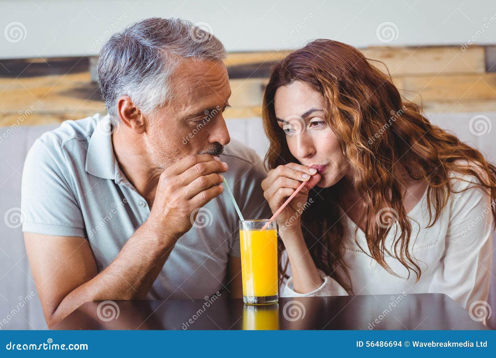 Couples mignons ayant le verre de jus d orange