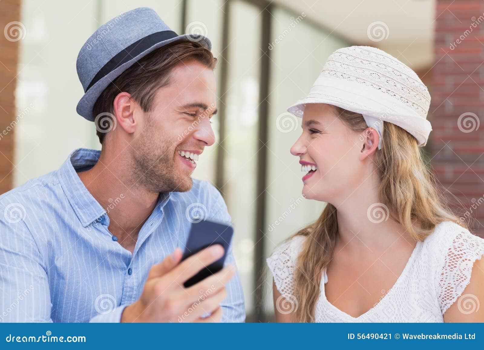 Couples mignons discutant au-dessus du smartphone