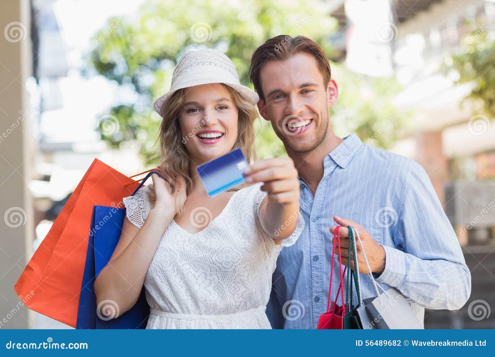 Couples mignons montrant une carte de crédit
