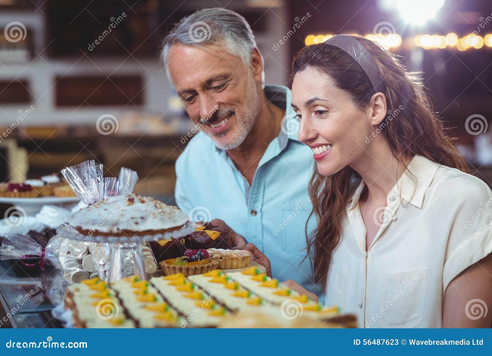 Couples mignons regardant des gâteaux