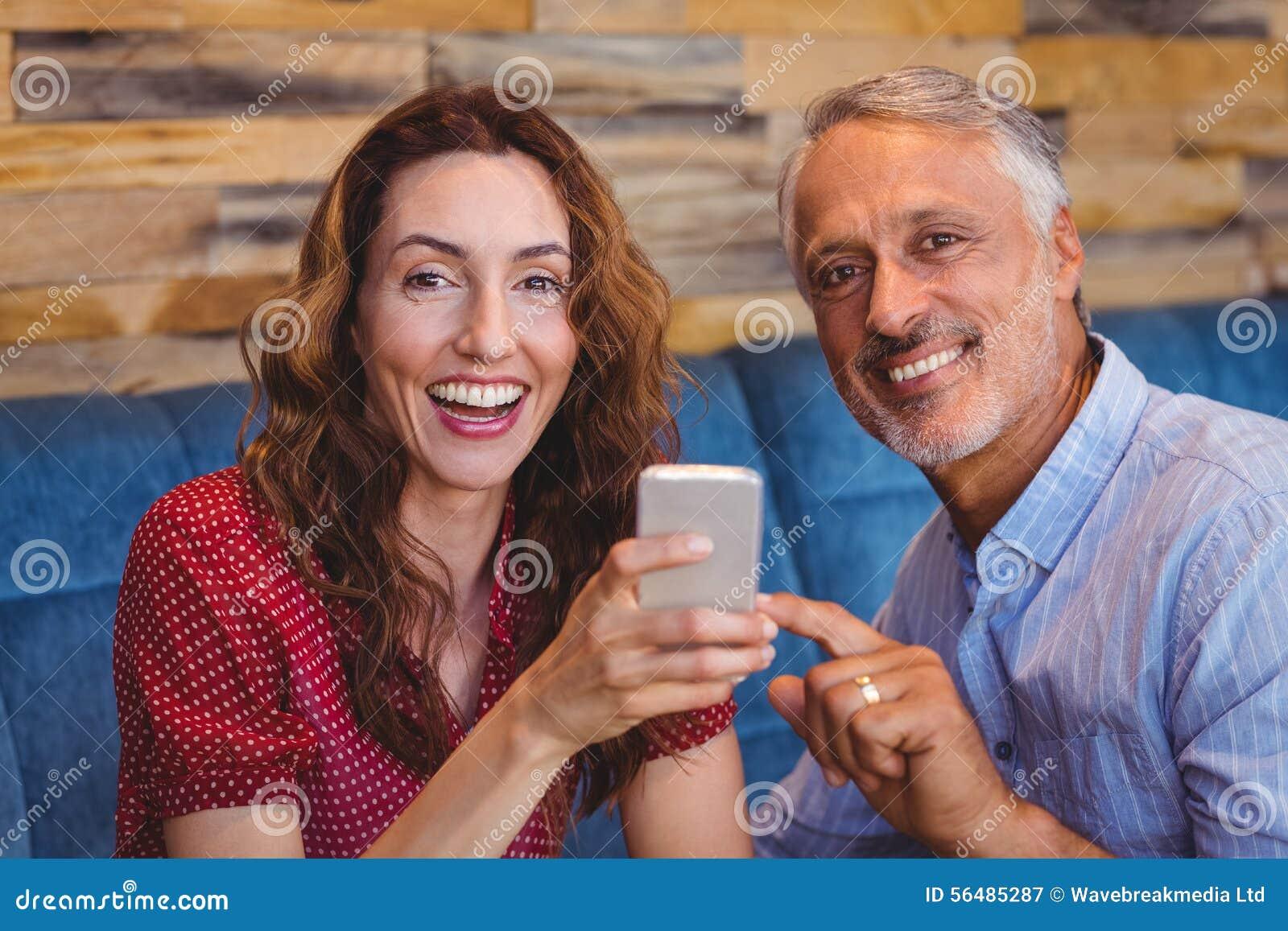 Couples mignons regardant leurs téléphones