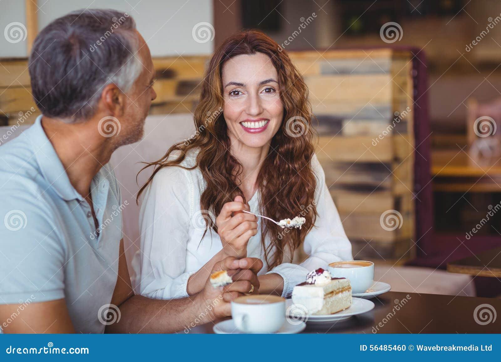Couples occasionnels ayant le café et le gâteau ensemble