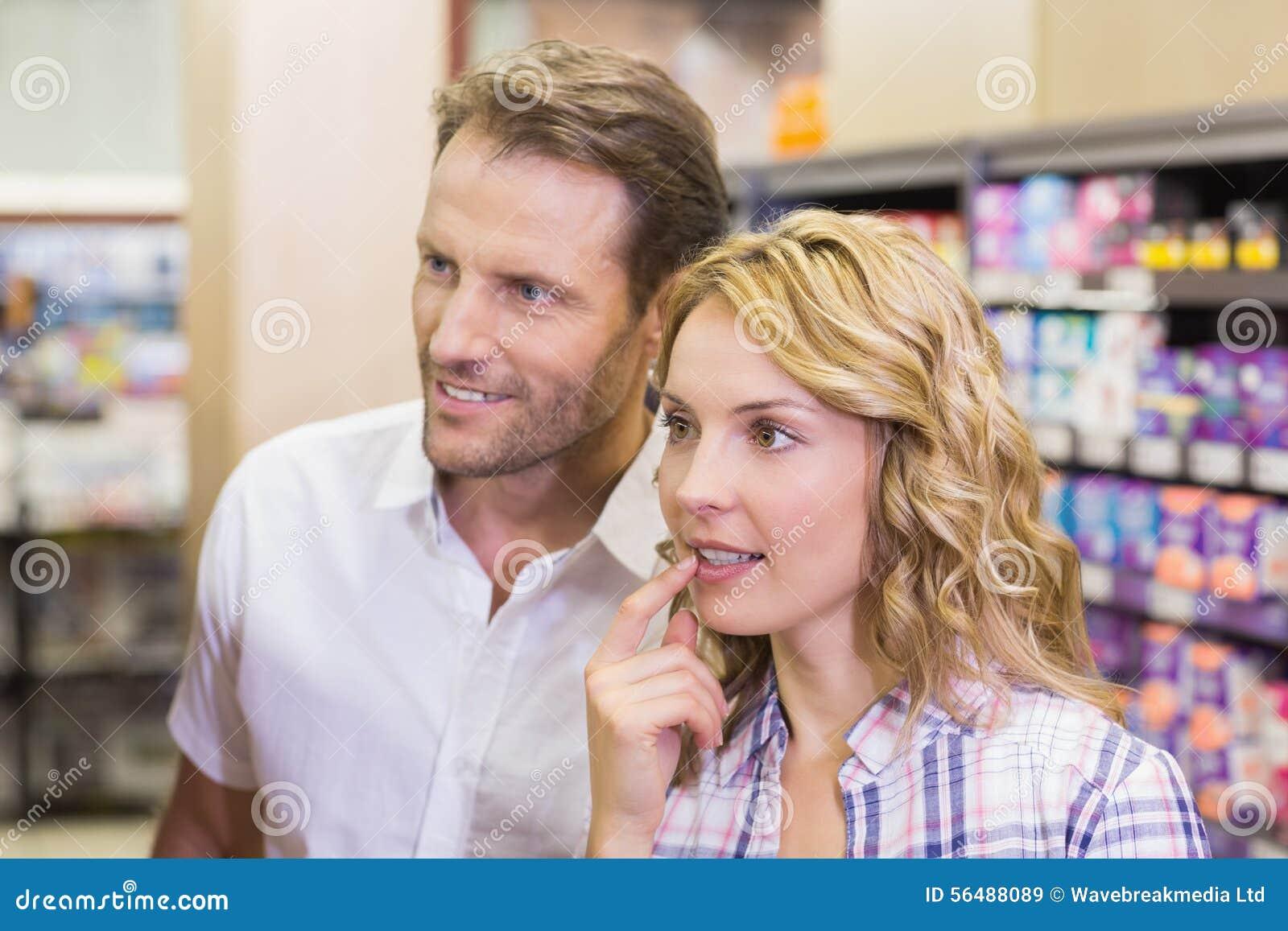 Couples occasionnels de sourire regardant l étagère