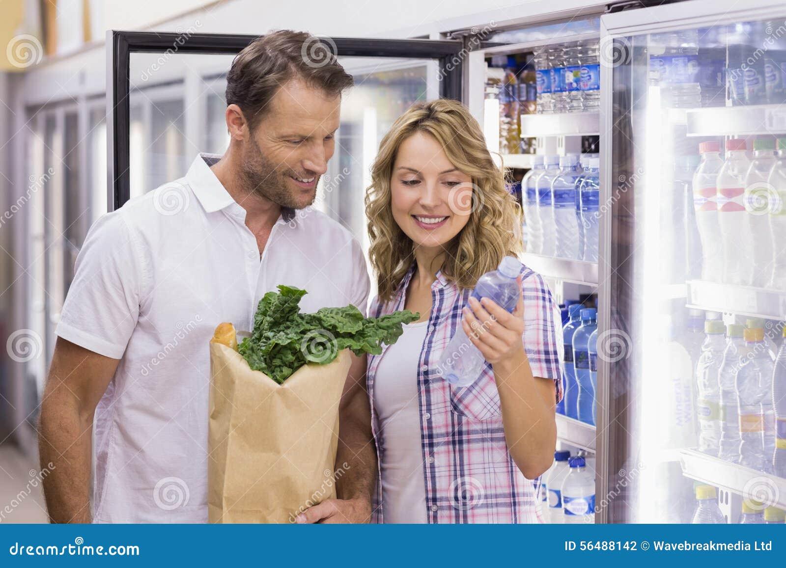 Couples occasionnels de sourire regardant la bouteille d eau