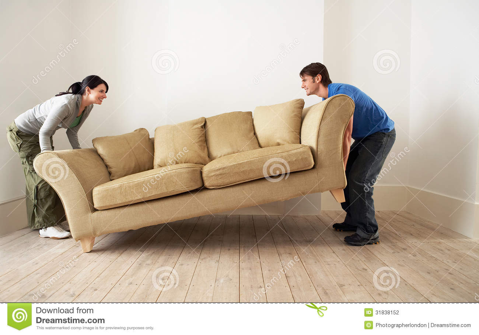 Couples plaçant la nouvelle maison de Sofa In Living Room Of