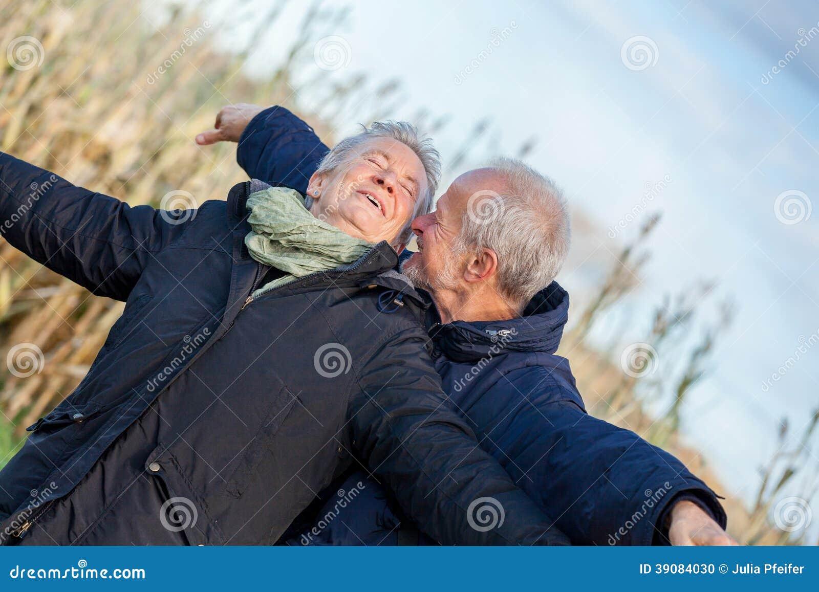 Couples pluss âgé embrassant et célébrant le soleil