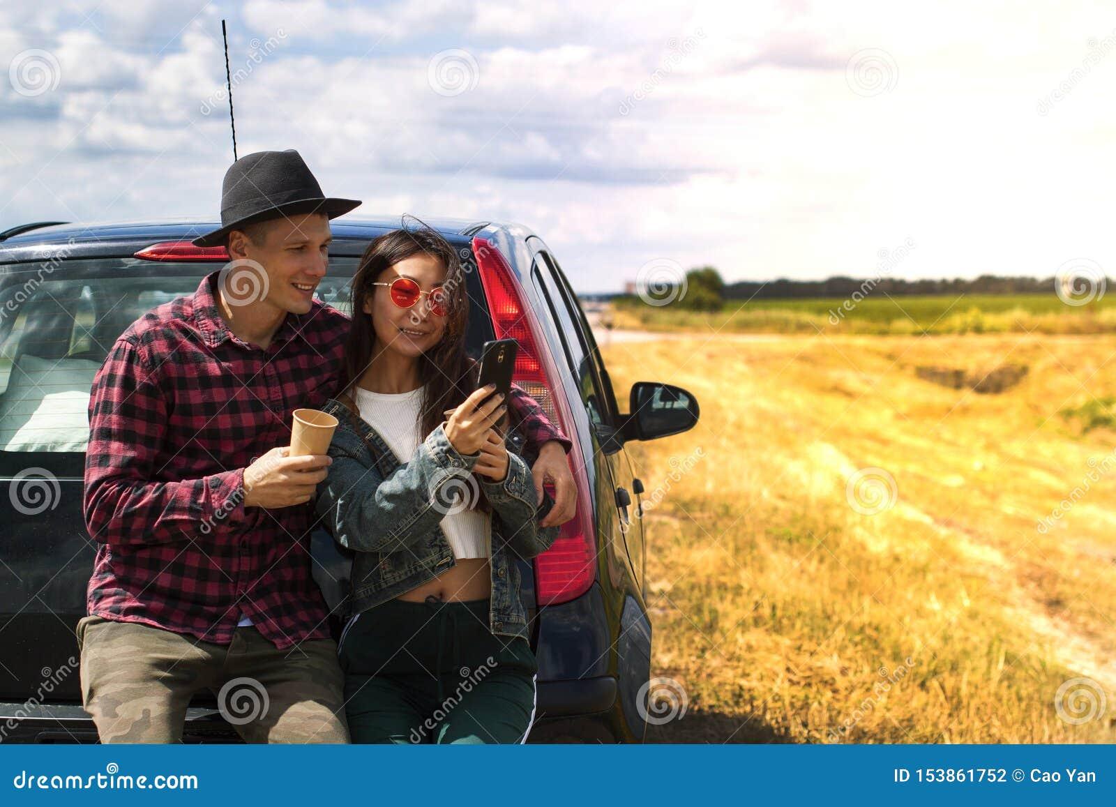 Couples près de ciel bleu de nature extérieure futée de téléphone de prise de femme de route de campagne de voiture