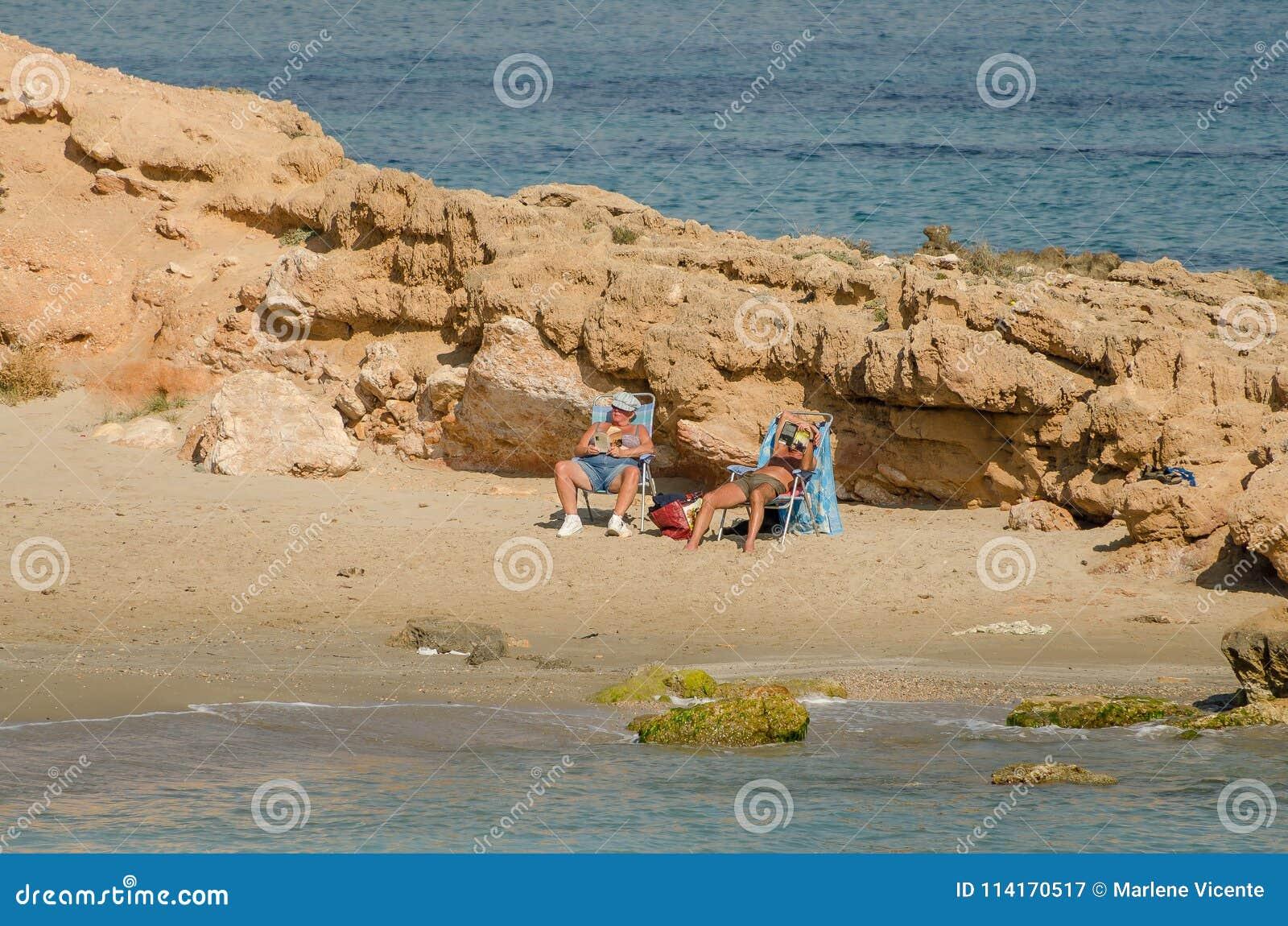Couples prenant un bain de soleil sur une plage