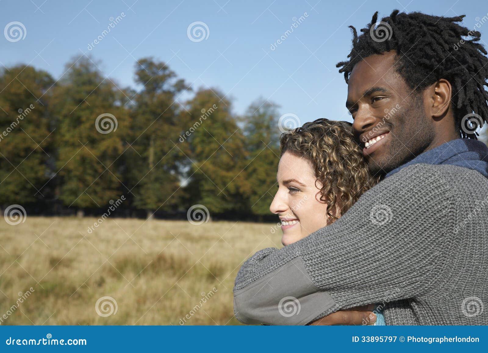 Couples réfléchis semblant partis tout en embrassant dans le domaine