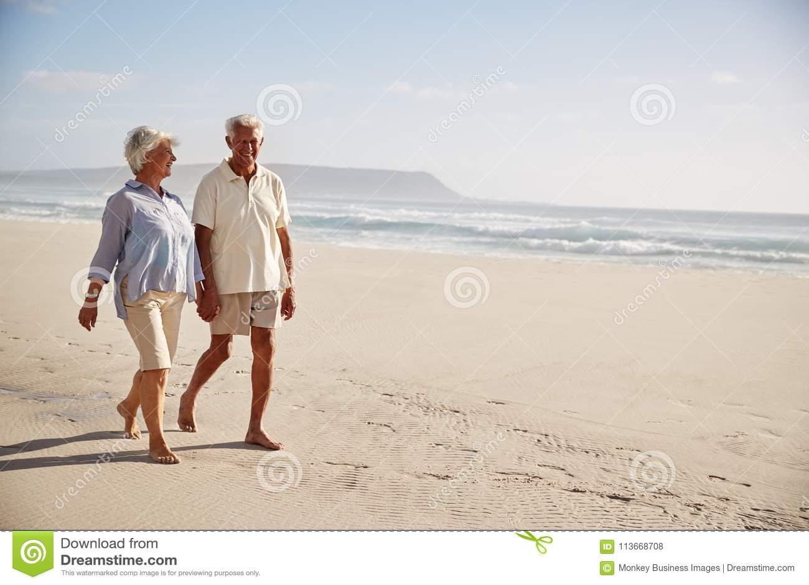 Couples retirés par aîné marchant le long de la plage de pair ensemble