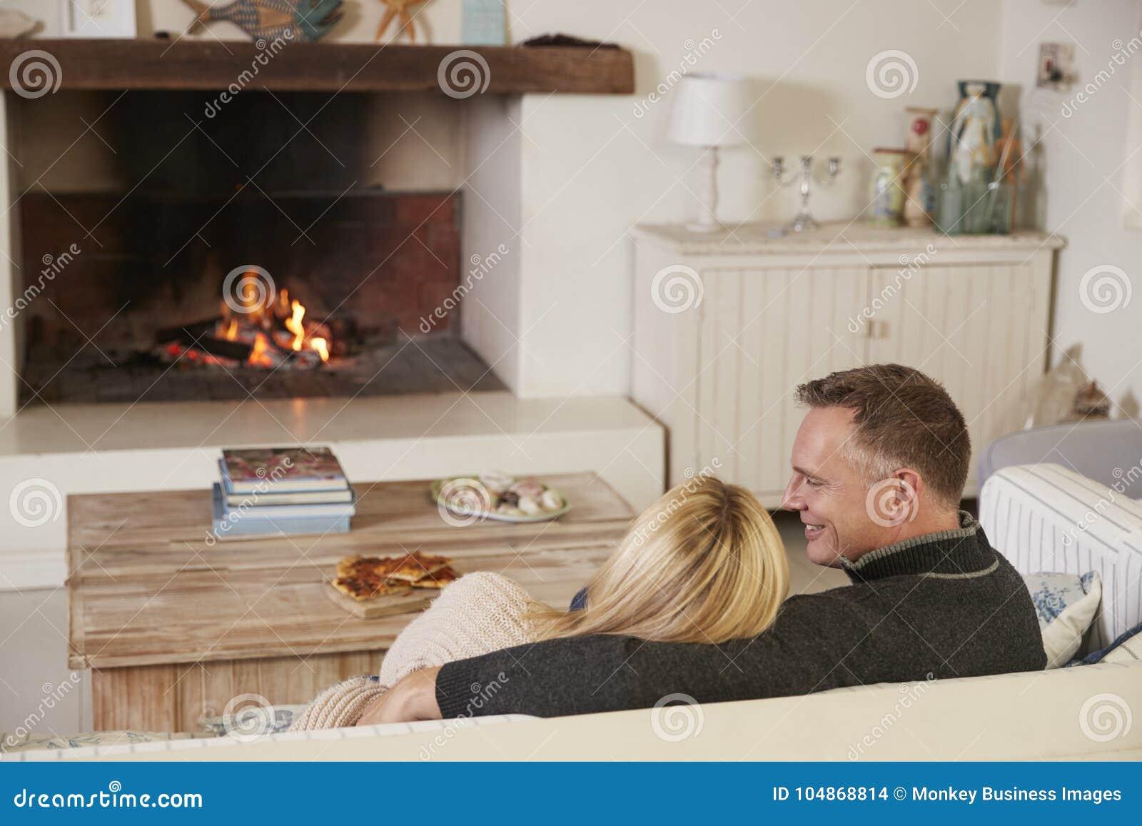 Couples romantiques détendant dans le salon à côté du feu ouvert