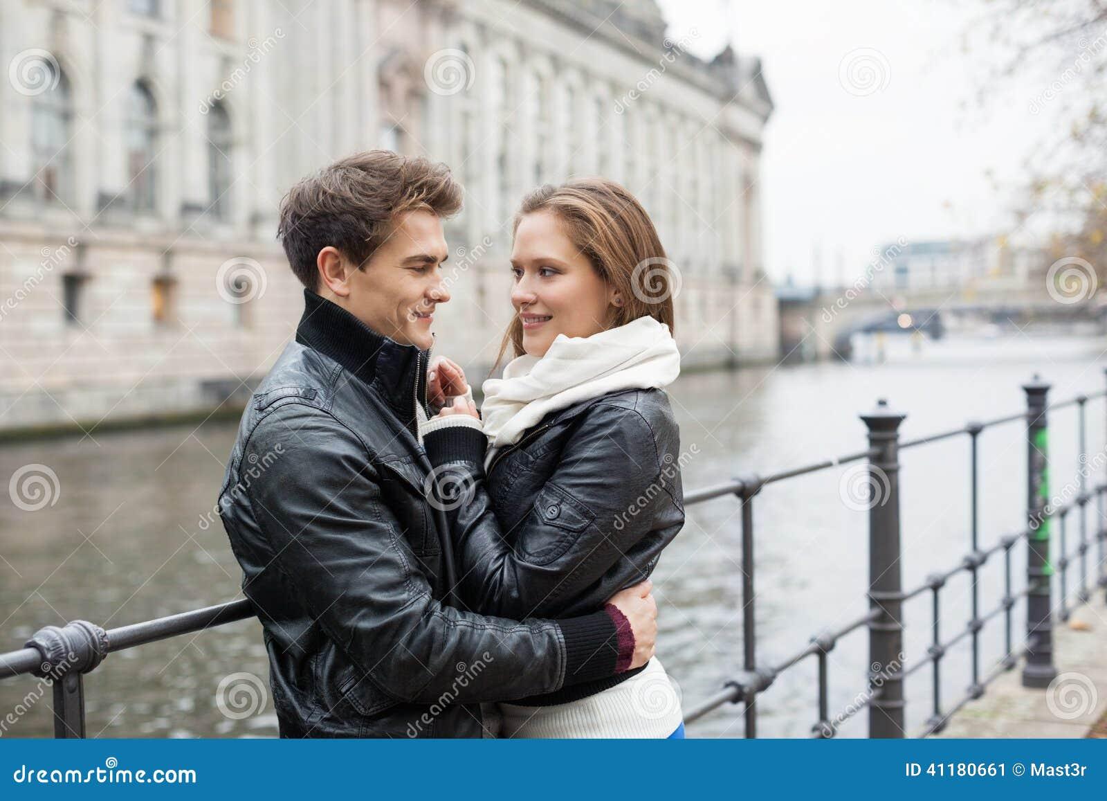 Couples romantiques dans des vestes embrassant par chemin de fer