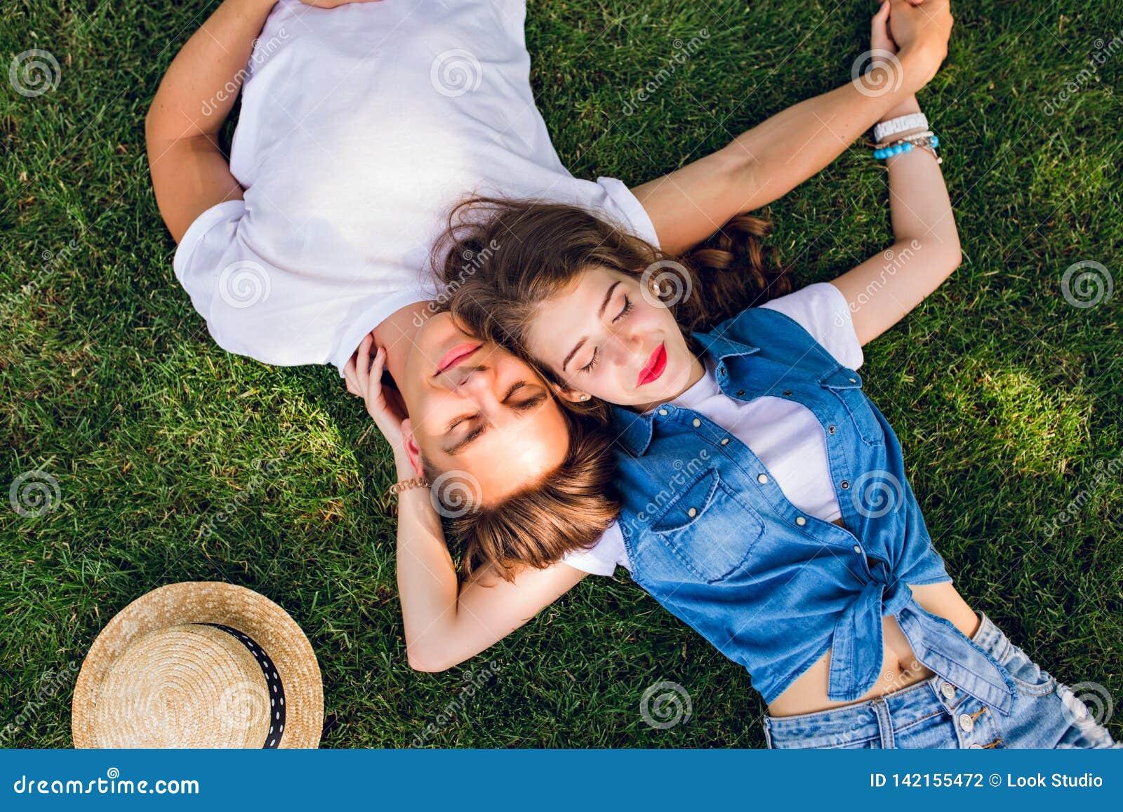 Couples romantiques des jeunes se trouvant sur l herbe en parc Ils s étendent sur les épaules de l un l autre et tiennent des mai